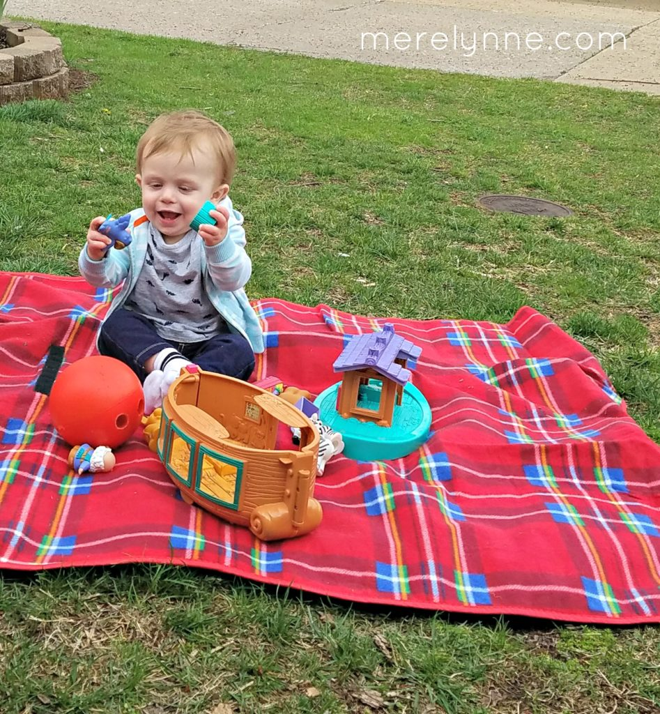 baby playing on picnic blanket, being sick as an adult